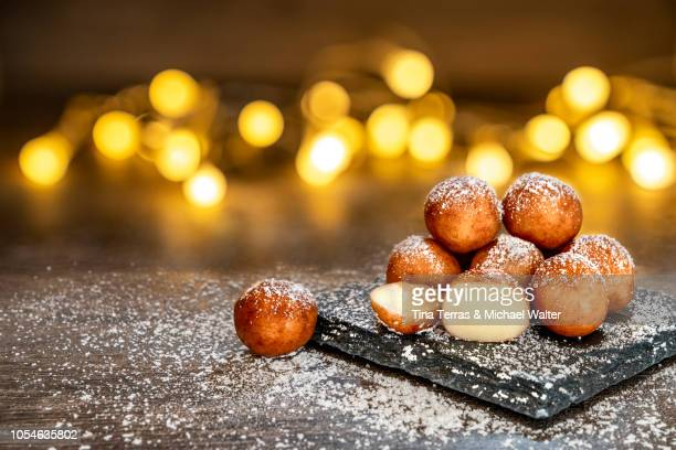 marzipan balls with powdered sugar on wooden board with slate plate and candlelight. - marzipan stock pictures, royalty-free photos & images