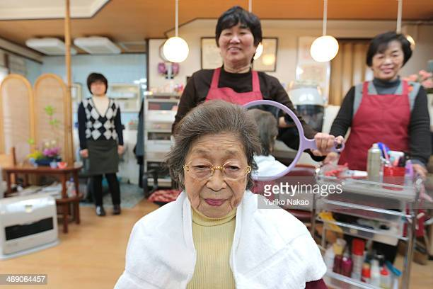 Masa Narita who just turned 100 years old on February 7 gets her hair set by a hairdresser at a beauty salon near her house on February 12 2014 in...