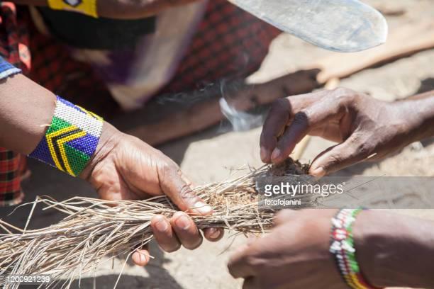 masaai warriors's hands making fire - fotofojanini foto e immagini stock