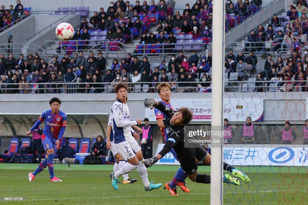 Masaaki Higashiguchi of Gamba Osaka saves a shot by Kosuke Ota of FC Tokyo during the J.League J1 match between FC Tokyo and Gamba Osaka at Ajinomoto Stadium on December 2, 2017 in Chofu, Tokyo, Japan.