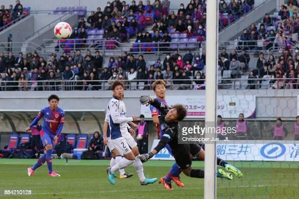 Masaaki Higashiguchi of Gamba Osaka saves a shot by Kosuke Ota of FC Tokyo during the JLeague J1 match between FC Tokyo and Gamba Osaka at Ajinomoto...