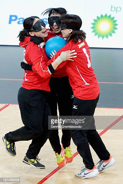 Masae Komiya of Japan celebrates with her teammates Rie Urata and Akiko Adachi after winning their Women's Team Goalball Gold Medal match against...