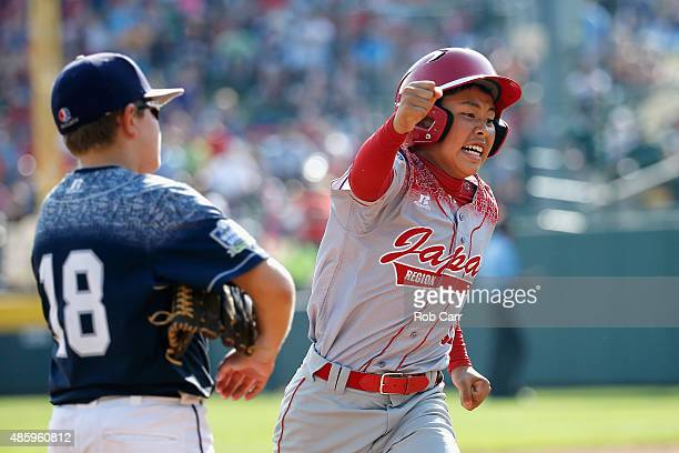 Masafuji Nishijima of team Japan celebrates while rounding the bases in front of Dylan Rodenhaber of the MidAtlantic team from Red Land Little League...