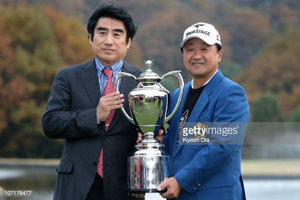 Masahiro Kuramoto of Japan and Haruhisa Handa Chairman of the International Sports Promotion Society pose with the tournament trophy during an award...