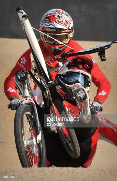 Masahiro Sampei of Japan succumbs to a fall as the handlebars and front wheel of his BMX bike detach in front of Alex hunter of Hong Kong as he...