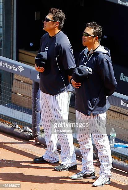 Masahiro Tanaka and Hiroki Kuroda of the New York Yankees stand during the playing of 'God Bless America' during the seventh inning against the...