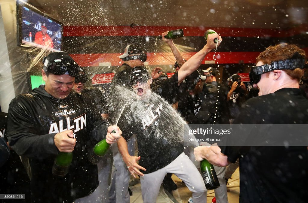 Masahiro Tanaka #19 of the New York Yankees and teammates celebrate in the locker room after their 5 to 2 win over the Cleveland Indians in Game Five of the American League Divisional Series at Progressive Field on October 11, 2017 in Cleveland, Ohio.