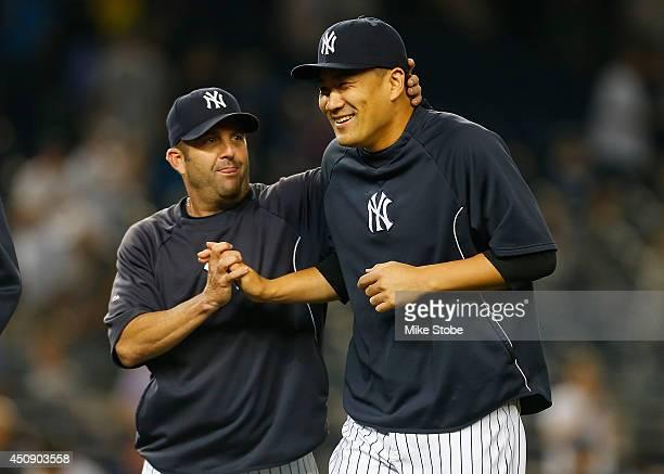 Masahiro Tanaka of the New York Yankees celebrates with batting coach Kevin Long after defeating the Toronto Blue Jays 6-4 at Yankee Stadium on June...