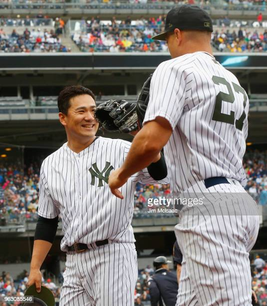 Masahiro Tanaka of the New York Yankees greets teammate Giancarlo Stanton after his catch ended the sixth inning against the Los Angeles Angels of...