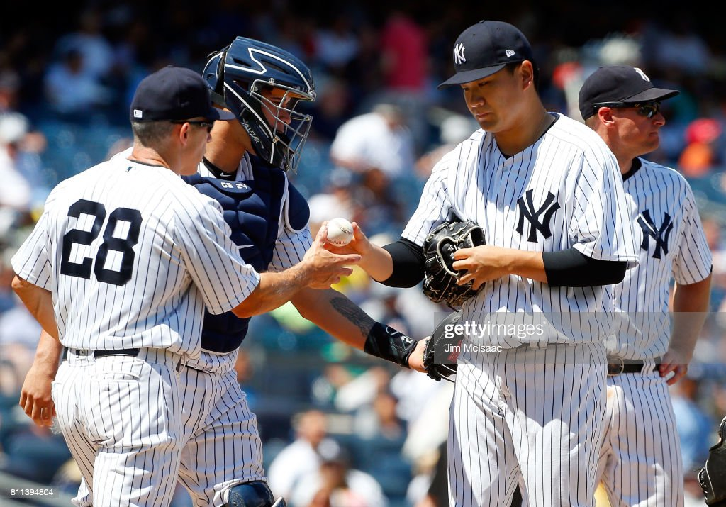 Masahiro Tanaka #19 of the New York Yankees hands the ball to manager Joe Girardi #28 as he is removed from a game against the Milwaukee Brewers during the fifth inning at Yankee Stadium on July 9, 2017 in the Bronx borough of New York City.