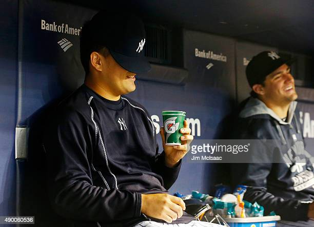 Masahiro Tanaka of the New York Yankees has a laugh in the dugout during the sixth inning of a game against the Chicago White Sox with teammate...