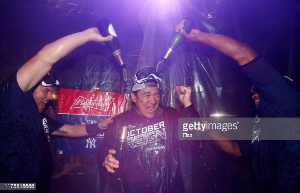 Masahiro Tanaka of the New York Yankees is doused with champagne by teammates Austin Romine and Cameron Maybin after the New York Yankees clinched...