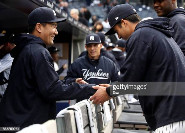 Masahiro Tanaka of the New York Yankees is greeted by teammates in the dugiut before the game against the Tampa Bay Rays on April 13 2017 at Yankee...