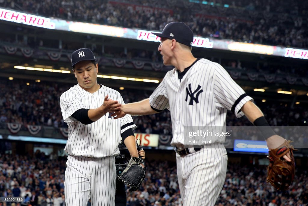 Masahiro Tanaka #19 of the New York Yankees is greeted by Todd Frazier #29 after striking out Marwin Gonzalez #9 of the Houston Astros to end the top of the seventh inning during Game 5 of the American League Championship Series at Yankee Stadium on Wednesday, October 18, 2017 in the Bronx borough of New York City.