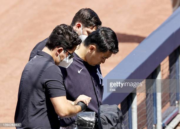 Masahiro Tanaka of the New York Yankees is helped off the field after he was hit by a batted ball during summer workouts at Yankee Stadium on July...
