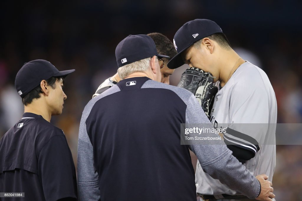 Masahiro Tanaka #19 of the New York Yankees is visited on the mound by pitching coach Larry Rothschild #58 and an interpreter in the sixth inning during MLB game action against the Toronto Blue Jays at Rogers Centre on September 22, 2017 in Toronto, Canada.