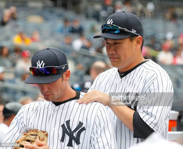 Masahiro Tanaka of the New York Yankees jokes with Greg Bird by massaging his shoulders in the dugout before the start of the first inning against...