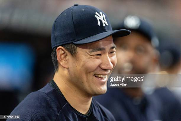 Masahiro Tanaka of the New York Yankees laughs with teammates in the dugout during the eighth inning against the Cleveland Indians at Progressive...