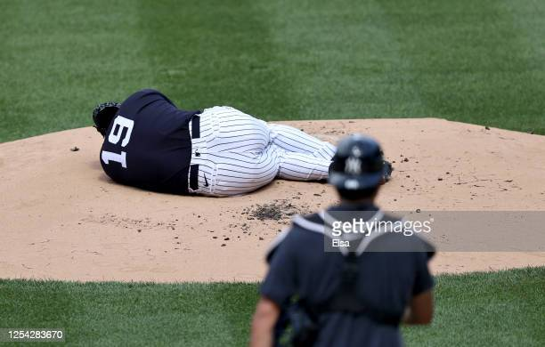 Masahiro Tanaka of the New York Yankees lies on the pitcher's mound after he was hit during summer workouts at Yankee Stadium on July 04, 2020 in New...