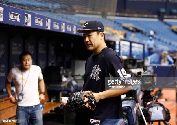Masahiro Tanaka of the New York Yankees makes his way into the dugout after speaking to the media before the start of a game against the Tampa Bay...