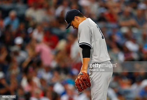 Masahiro Tanaka of the New York Yankees reacts after walking Cameron Maybin of the Atlanta Braves in the first inning at Turner Field on August 28,...
