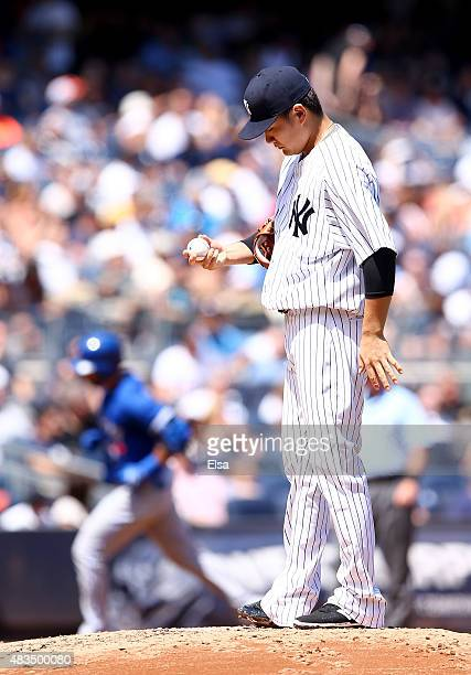 Masahiro Tanaka of the New York Yankees reacts as Jose Bautista of the Toronto Blue Jays rounds the bases after a solo home run in the fourth inning...