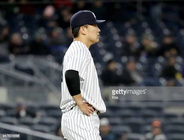 Masahiro Tanaka of the New York Yankees reacts as JT Realmuto of the Miami Marlins rounds the bases after hitting a three run home run in the fifth...