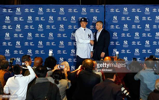 Masahiro Tanaka of the New York Yankees shakes hands with manager Joe Girardi as he introduced to the media during a news conference on February 11...