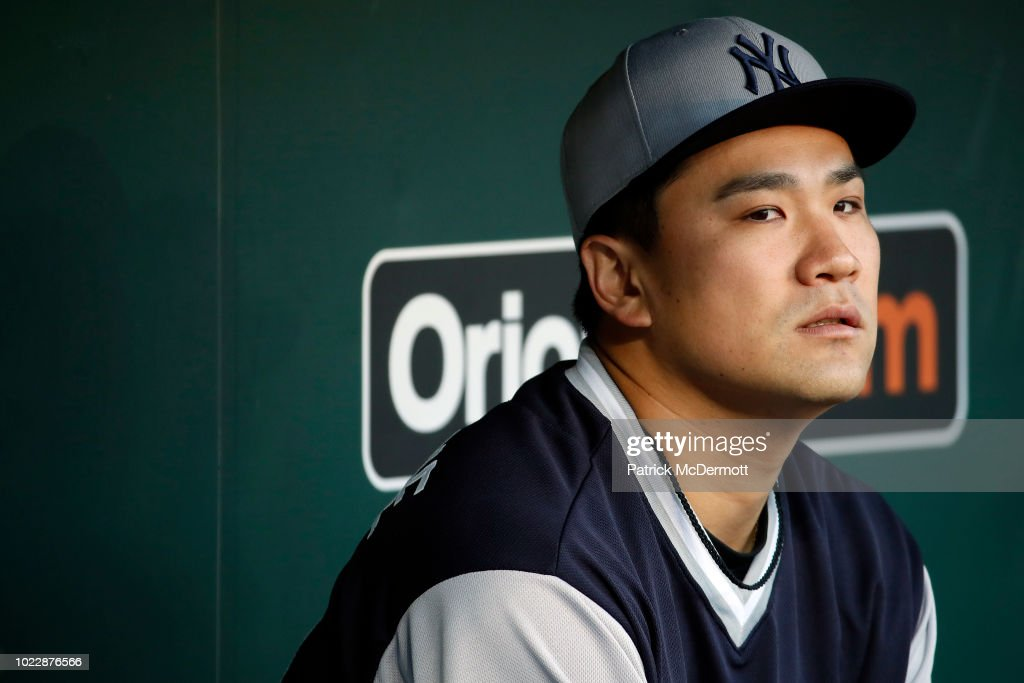 Masahiro Tanaka #19 of the New York Yankees sits in the dugout before a game against the Baltimore Orioles at Oriole Park at Camden Yards on August 24, 2018 in Baltimore, Maryland.