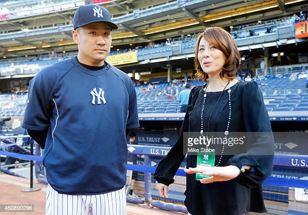 Masahiro Tanaka of the New York Yankees speaks with Japanese actress Ryoko Yonekura prior to the game against the Toronto Blue Jays at Yankee Stadium...