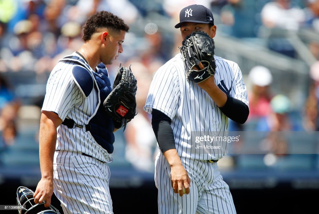 Masahiro Tanaka #19 (R) of the New York Yankees talks with teammate Gary Sanchez #24 during the third inning against the Milwaukee Brewers at Yankee Stadium on July 9, 2017 in the Bronx borough of New York City.