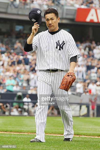 Masahiro Tanaka of the New York Yankees tips his cap to the fans after being taken out of the game in the sixth inning inning against the Toronto...