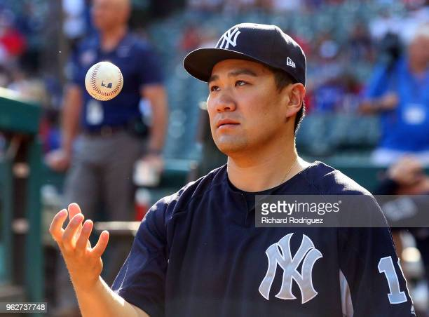Masahiro Tanaka of the New York Yankees tosses a baseball in the dugout before a baseball game against the Texas Rangers at Globe Life Park in...