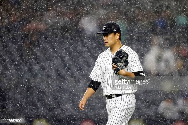 Masahiro Tanaka of the New York Yankees walks off the field as the tarp is put on the field for a rain delay against the Seattle Mariners at Yankee...