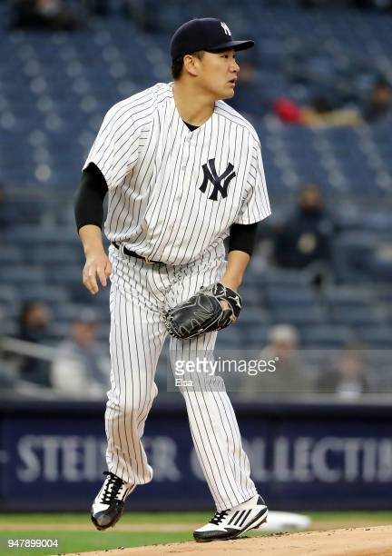 Masahiro Tanaka of the New York Yankees watches a hit by JT Realmuto of the Miami Marlins in the first inning against the Miami Marlins at Yankee...
