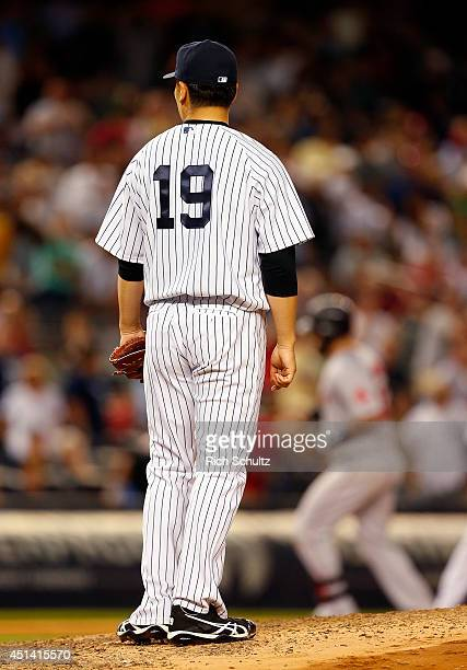 Masahiro Tanaka of the New York Yankees watches as Mike Napoli of the Boston Red Sox rounds third base after hitting a home run in the ninth inning...