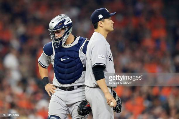 Masahiro Tanaka talks to Gary Sanchez of the New York Yankees after Sanchez was hit in the leg by a pitch in the third inning against the Houston...