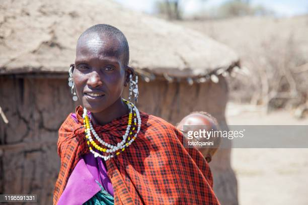 masai baby carried by his mother tanzania - fotofojanini foto e immagini stock