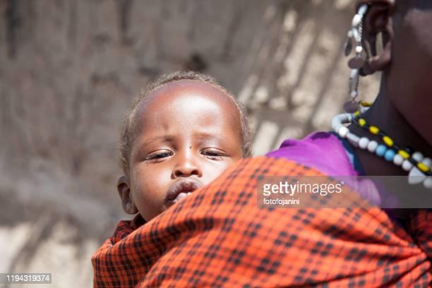 masai baby carried by mother - fotofojanini foto e immagini stock