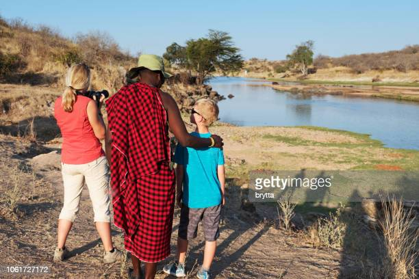 Masai guide and tourists near the river
