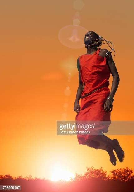 Masai man jumping while performing a Masai traditional dance, Masai Mara National Reserve, Kenya