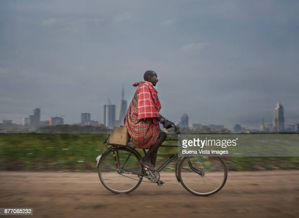 Masai man riding a bicycle on a country road.