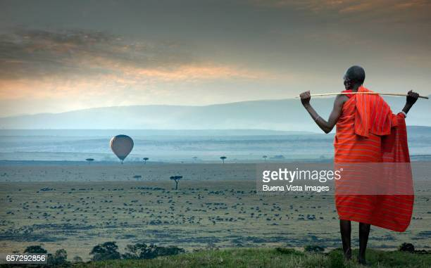 masai man watching a hot-air balloon over the savannah - kenia fotografías e imágenes de stock