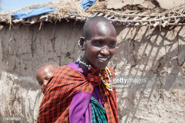 masai mother carries her baby - fotofojanini foto e immagini stock