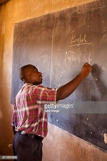 masai teacher writing in english in rural schoolroom - jake warga stock pictures, royalty-free photos & images