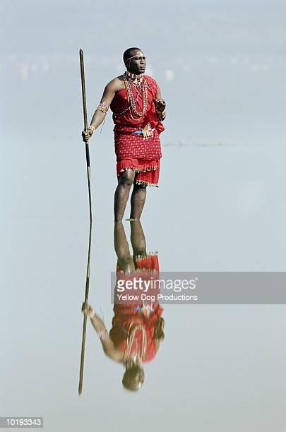 Masai warrior standing in water, Nakuru Park, Kenya