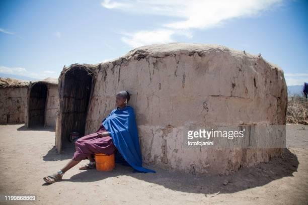 masai woman in her  traditional clothes outside her mud hut - fotofojanini foto e immagini stock
