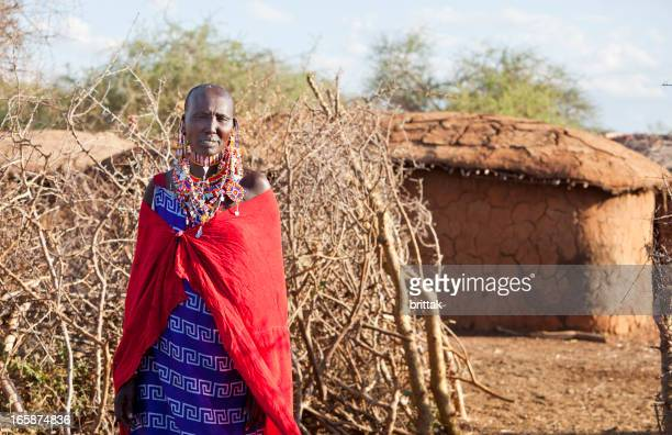 Masai woman in traditional dress and jewellry stading outside village.