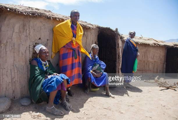 masai women in a traditional village  outside their mud hut - fotofojanini foto e immagini stock