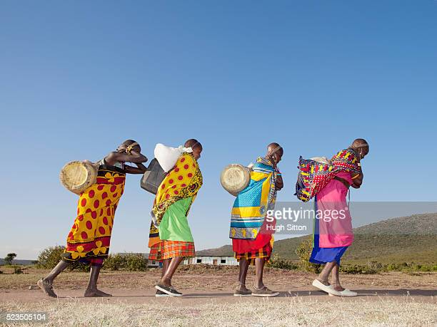 masai women in traditional clothing carrying water containers - hugh sitton stock-fotos und bilder